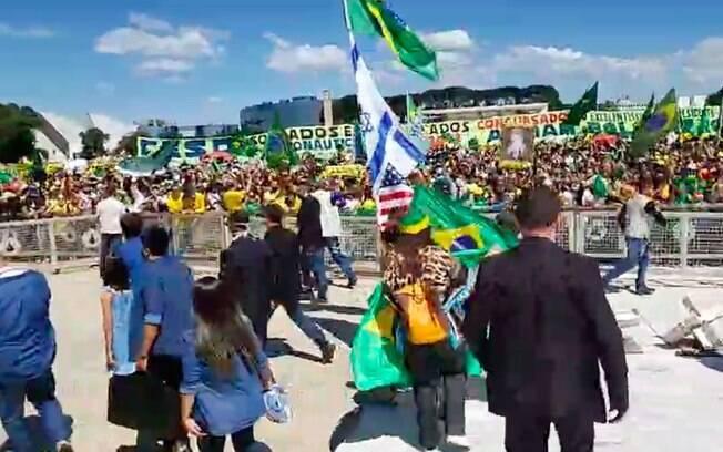Durante manifestação, Um dos acompanhantes do presidente empunha um mastro com as bandeiras dos Estados Unidos, de Israel e do Brasil