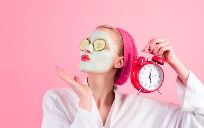 mulher com máscara facial e segurando um relógio