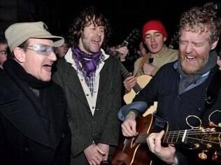 Bono canta ao lado dos amigos em uma rua de Dublin