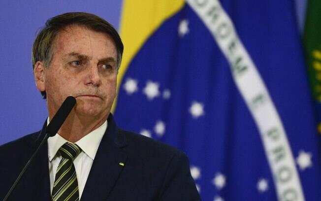 homem diante da bandeira do brasil