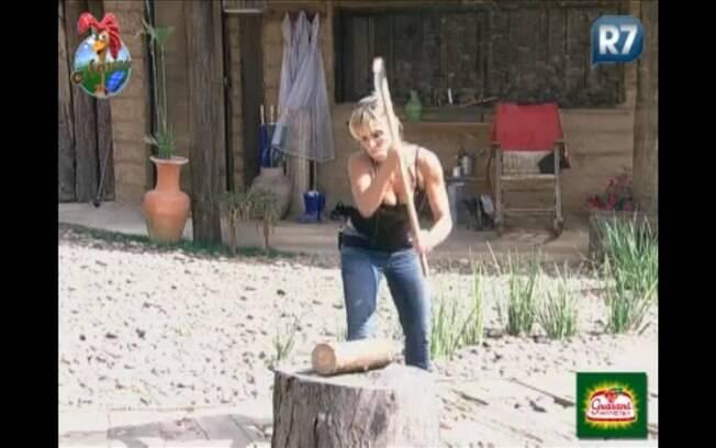 Anna Markun tenta cortar lenha na Casa da Roça