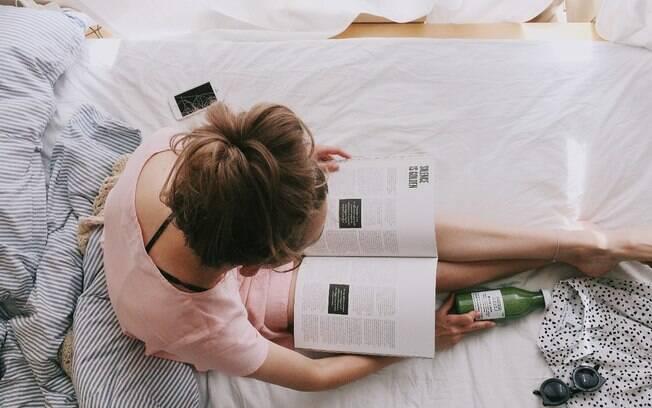 mulher lendo revista na cama