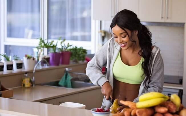 mulher na cozinha cortando fruta