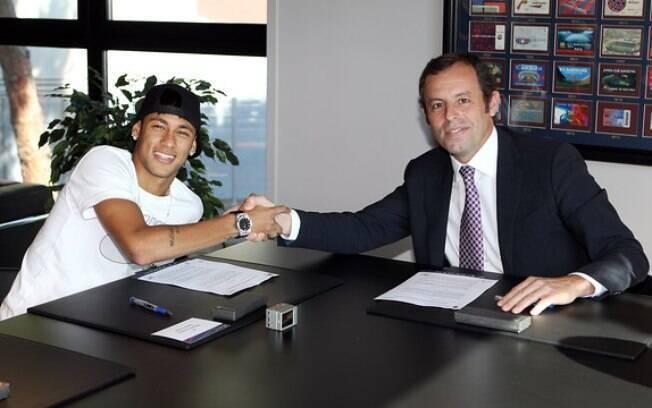 Neymar assina o contrato ao lado do  presidente do Barcelona, Sandro Rosell