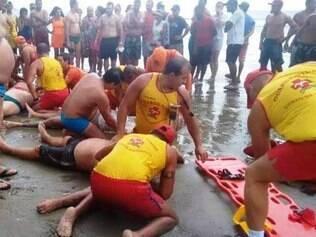Bombeiros tentam reanimar vítimas atingidas por um raio na orla de Praia Grande, em São Paulo