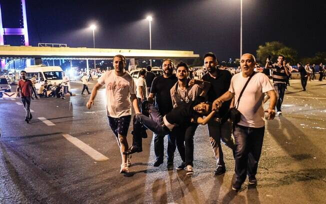 Homem baleado é acolhido por pessoas durante confrontos com militares na Ponte Bosphorus, em Istambul