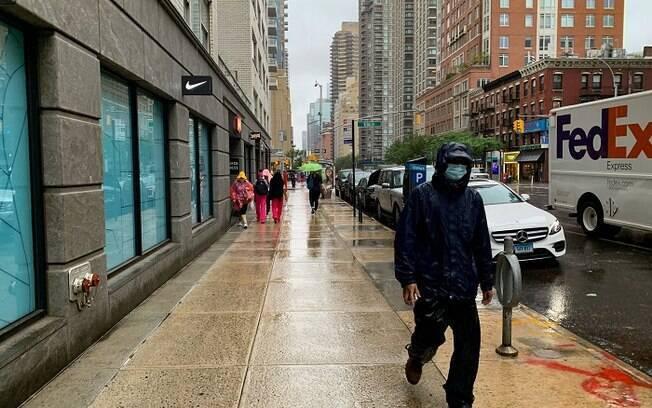 Moradores caminham com máscaras em Nova York