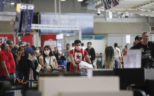 pessoas num aeroporto se protegendo, usando mascaras
