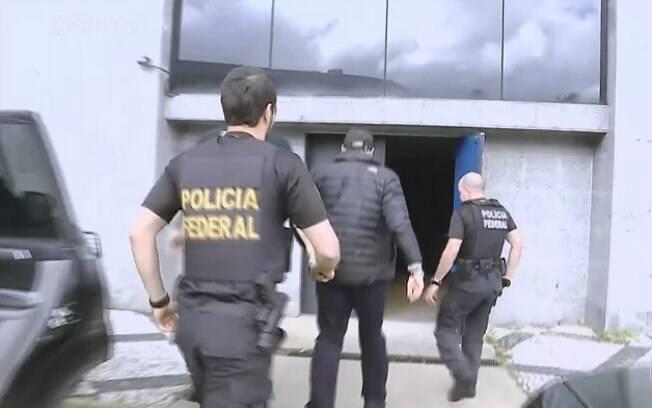 De boné e jaqueta pretos, Guido Mantega chegou à sede da Polícia Federal em São Paulo e será transferido para Curitiba