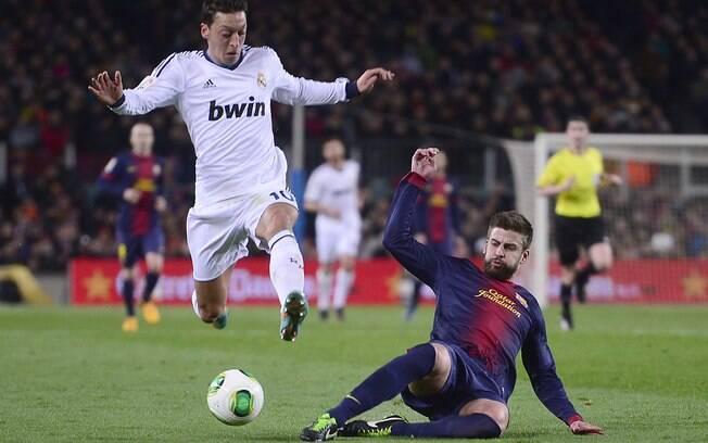 Özil escapa de carrinho de Piqué