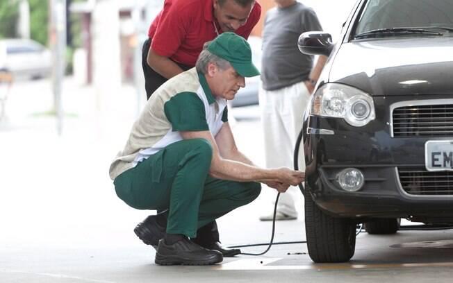 O apresentador calibra pneu de um carro...