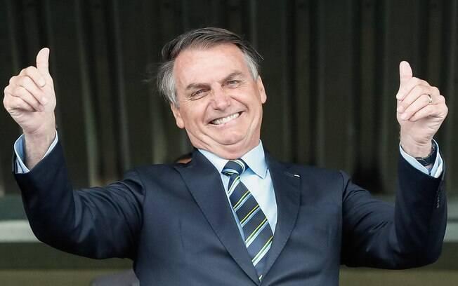 Jair Bolsonaro sorrindo e fazendo joinha com as duas mãos