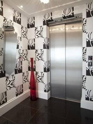 No projeto da arquiteta Orlane Santos a composição preta-e-branca feita com papel e o vaso vermelho dão vida ao local