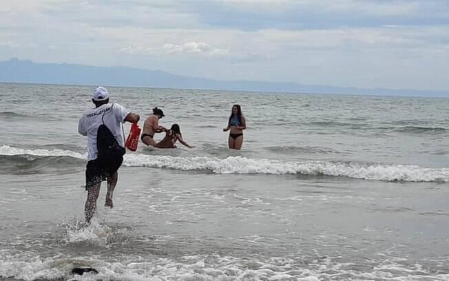 Momento em que fiscal da Vigilância Sanitária tentou socorrer idosa e criança no mar.