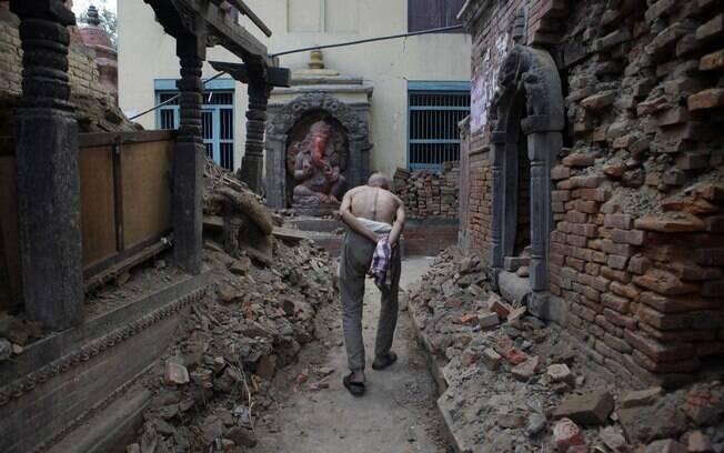 Um idoso anda pelo que restou de templo após fim do período de luto pela morte de um membro de sua família em Bhaktapur