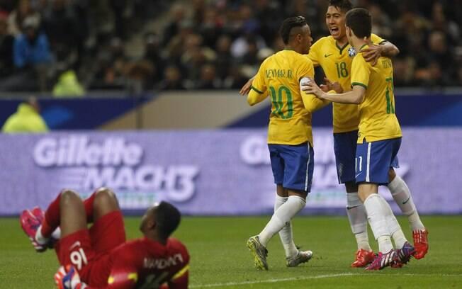 Firmino e Neymar comemoram com Oscar o gol de empate da seleção brasileira diante da França, no Stade de France
