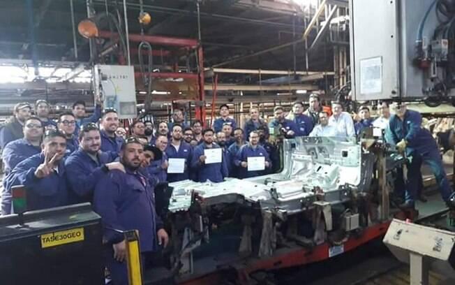 Funcionários posam ao lado do chassi do último Ford Focus, colocando fim na história de duas décadas