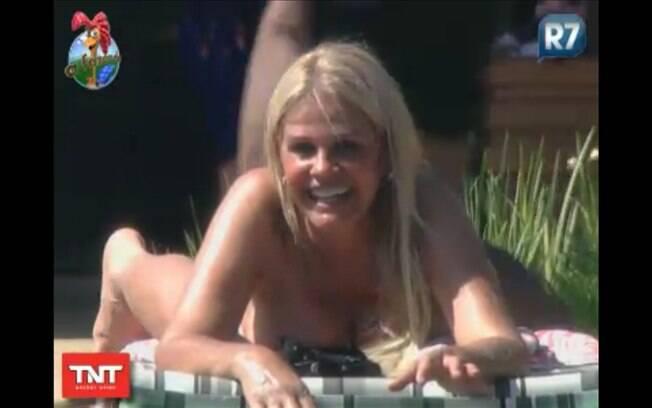 De bruços e com a parte de cima do biquíni solta, Monique toma sol quase de topless