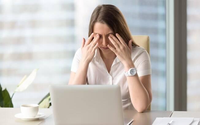 Mulher esfregando os olhos em frente a computador