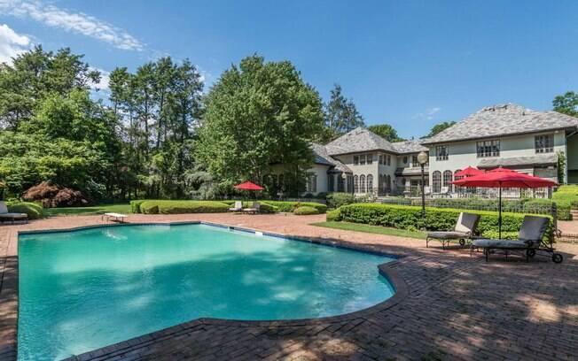 A área externa da mansão tem piscina, um lago e uma garagem para três carros