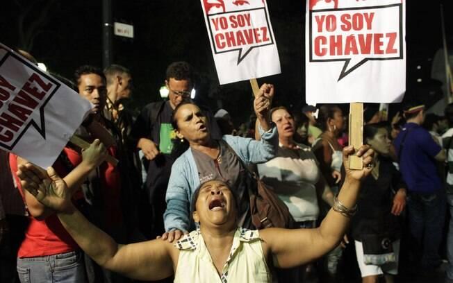 Partidários do presidente Hugo Chávez choram enquanto seguram cartazes em que se lê 'Eu sou Chávez' durante homenagem a líder venezuelano na Praça Bolívar, Caracas (05/03)