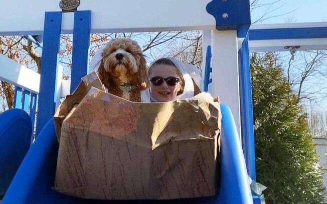 Sadia Gubenko e o cachorro da família descendo em um escorregador de brinquedo enquanto estão dentro de uma caixa de papelão, simulando uma montanha russa.