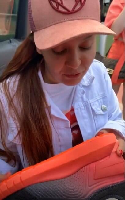 Maiara segurando tênis que comprou para Fernando