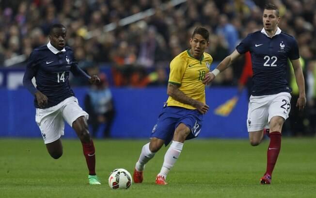 Estreante como titular da seleção brasileira, Roberto Firmino é cercado por dois franceses
