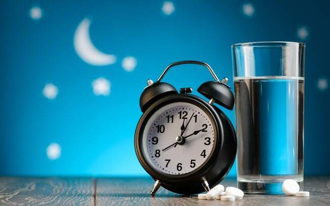 Alarme ao lado de copo d'água e pílulas de remédio em frente a um papel de parede estrelado