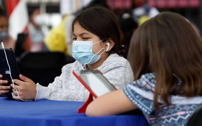 Criança com máscara olha para um celular