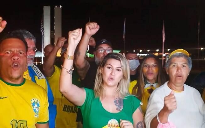 mulher de verde e amarelo na frente de publico