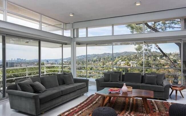 O piso e as paredes claras contrastam com elementos de tons mais sólidos e fortes, como estofados, tapetes e móveis