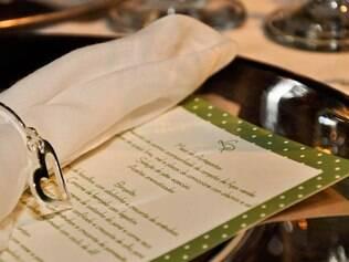 Nas mesas, cardápio com moldura em poá sobre as toalhas verdes