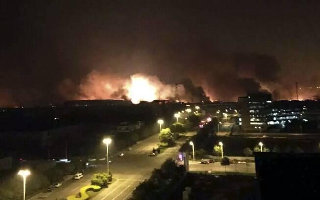 Labaredas são vistas nas proximidades onde ocorreu explosões na China (12/08). Foto: AP