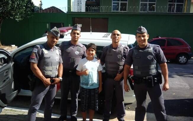 Pequeno Cauã e equipe da Polícia Militar que realizou o resgate