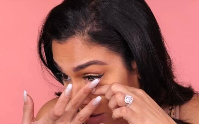 Antes de finalizar o truque de maquiagem Huda acrescenta um passo opcional: colocar lentes de contato em cores claras
