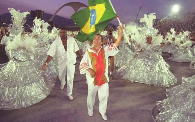 Joãosinho Trinta leva uma bandeira do Brasil na Marquês de Sapucaí em 1997