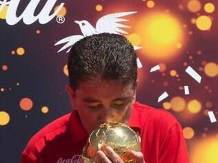 Brazil's former World Cup soccer champion Bebeto kisses the FIFA World Cup trophy at the opening ceremony of the FIFA WCUP Trophy Tour in Rio de Janeiro, Brazil, Thursday, Sept. 12, 2013. The trophy is set to embark on an extensive journey, covering more than 80 countries, giving the opportunity to millions of fans to enjoy the authentic solid-gold trophy. Brazil will host the World Cup soccer tournament in 2014. (AP Photo/Silvia Izquierdo)
