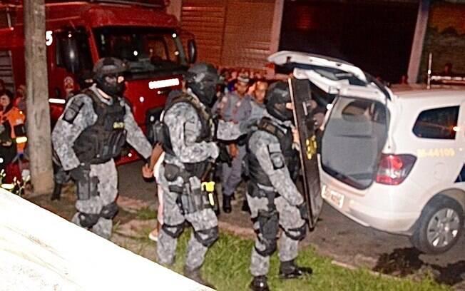 Final de ocorrência: o agressor é preso e conduzido para a viatura. Note o PM do GATE à esquerda segurando as mãos algemadas do padrasto. Ao fundo, e mais à esquerda, Bombeiros e Resgate de prontidão