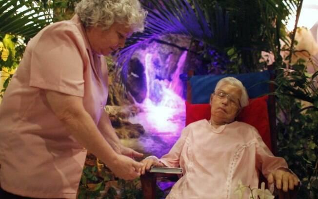 Sentada, Porto Rico: Dolores Lamboy toca a mão de sua mãe, Georgina Chervony, cujo corpo foi posto em cadeira de balanço para seu velório em maio. Foto: AP
