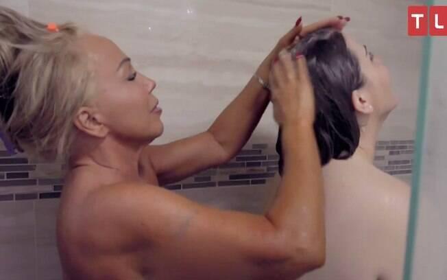 Mary lavando o cabelo da sua filha, Brittani, no chuveiro.