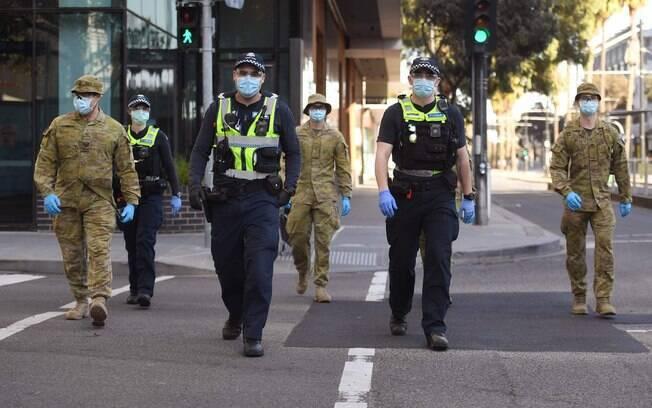 Um grupo de policiais e soldados patrulha em Melbourne, na Austrália, após o anúncio de novas restrições para conter a propagação do novo coronavírus