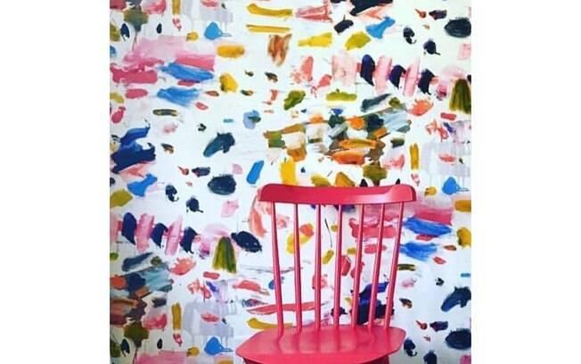 O papel de parede com ar de aquarela é um belo pano de fundo para a cadeira rosa. Solução simples e descontraída.