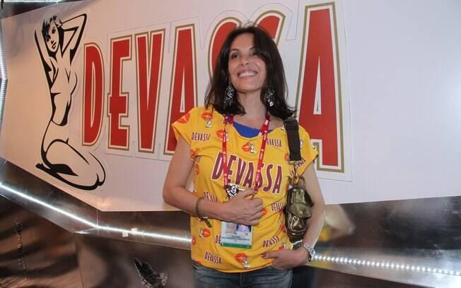 Carolina Ferraz tentou desfarçar e esconder a foto de sua credencial ao chegar ao camarote Devassa, na Sapucaí
