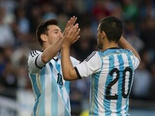 Argentina's Lionel Messi, left, celebrates with Argentina's Sergio Aguero after scoring against Slovenia at their international friendly soccer match in La Plata, Argentina, Saturday, June 7, 2014. Argentina's team is leaving June 9 for Brazil to compete in the World Cup. (AP Photo/Eduardo Di Baia)