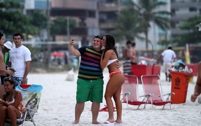 Nicole Bahls dá beijinho e faz pose para a foto do fã na praia