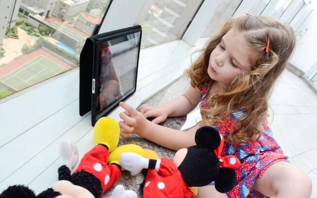 A pequena Pietra, de 4 anos, divide a atenção entre seus bonecos e o tablet da mãe