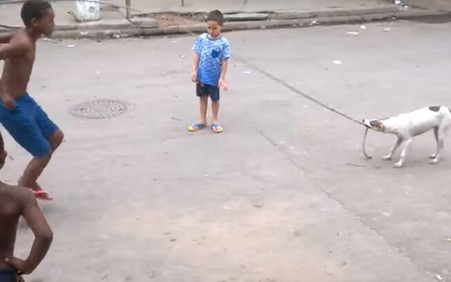 Crianças brincando de pular corda com ajuda de cachorrinha.