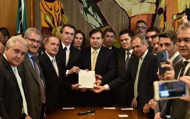 Ao lado de ministros, o presidente Jair Bolsonaro entregou a proposta de reforma da Previdência para Rodrigo Maia