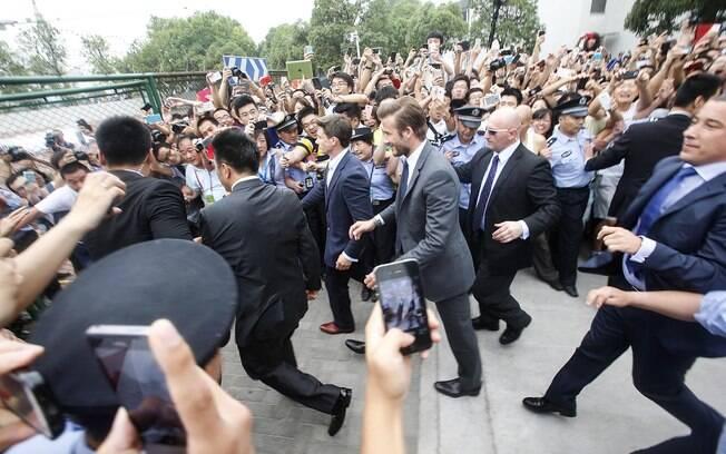 Beckham é cercado por policiais na saída do  evento na China
